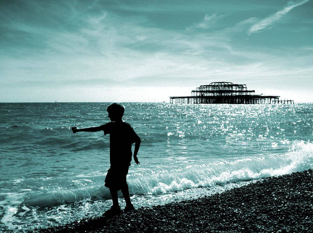 Boy Playing on the Beach with the West Pier in the Background at Brighton England