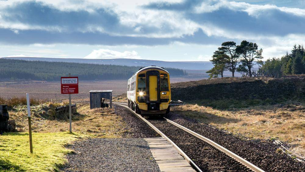 Train approaching Altnabreac railway station in the Scottish Highlands